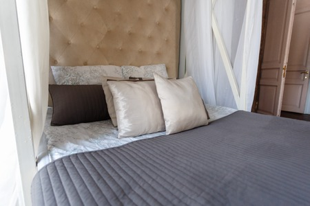 The made-up bed is covered with white clean pillows and bed linen. Four-poster bed in a stylish hotel room.