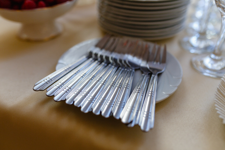 Clean Cutlery: forks in white plates and a blurred stack of plates in the background stand on a wooden shelf Фото со стока