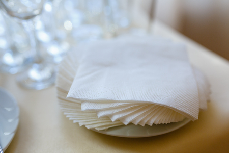 Paper napkins on white taralee in perspective isolated. Swipe close - up view from above. A stack of paper napkins with a shadow. Paper napkin on wooden table close - up view from above
