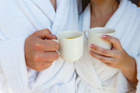 Happy young couple in white bathrobes drinking coffee and fresh juice together in bed in the morning. The couple meet in the morning at the hotel. Morning breakfast in the room.