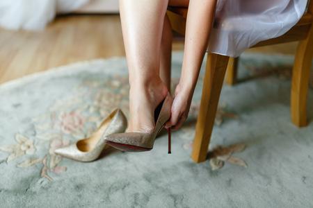 La niña se prueba hermosos zapatos caros de tacón alto en el dormitorio o en el hotel. Pies de novia en zapatos de boda, primer plano, cerrado.