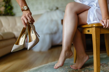 A mans hand delivers shoes girl. A young woman tries on beautiful expensive high-heeled shoes in a bedroom or hotel. Brides feet in wedding shoes, close-up, closed.