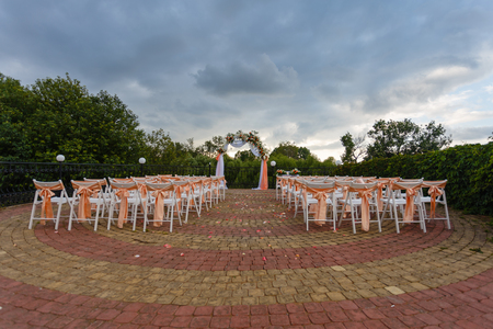 Open air decorated area for the wedding ceremony with a wooden arch decorated with flowers. White wooden chairs decorated with orange bows and roses outdoors on green grass background.