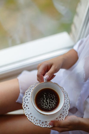 Girl in a Bathrobe sits on the windowsill next to the window and drinks coffee from a mug with a saucer. Young woman in a bathrobe drinking hot espresso or cappuccino in the morning on the windowsill. Фото со стока