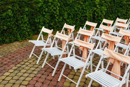 White wooden chairs decorated with orange bows and roses for holiday or anniversary ceremony in row outdoors on green grass background. Wedding and celebration 스톡 콘텐츠