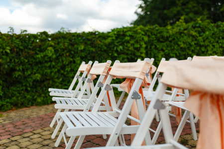 White wooden chairs decorated with orange bows and roses for holiday or anniversary ceremony in row outdoors on green grass background. Wedding and celebration Фото со стока