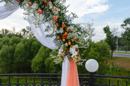 White flowers and greens on the wedding arch, rustic wedding arch decorated with flowers, stylish wedding decor. Open air decorated area for the wedding ceremony with a wooden arch decorated.