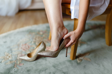 The girl tries on beautiful expensive high-heeled shoes in the bedroom or hotel. Brides feet in wedding shoes, close-up, closed.