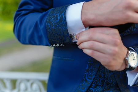 Businessman in a stylish blue suit with patterns adjusts the cuffs of his shirt. Stylish man in an expensive suit and tie and jacket, close-up. Unrecognizable. Stock Photo