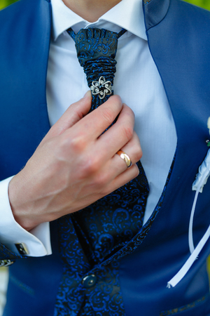 Businessman in a stylish blue suit with patterns straightens tie. Stylish man in an expensive suit and tie and jacket, close-up. Unrecognizable.