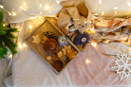 Wooden tray with ceramic kettle, a mug, gingerbread, toys, pillows on a cozy blanket lying on the bed in the lights of a garland. ?oncept of winter mood, the time of tea in bed, Christmas holiday