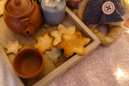 Wooden serving tray with brown ceramic kettle, steaming hot drink mug in a cozy home interior. Food, drinks, toy, gingerbread cookies. Concept enjoying autumn, winter mood, tea time, Christmas holiday