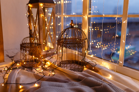 Cages for birds covered with garland with yellow lights. Cozy winter or autumn morning at home. Warm blanket, garland with lights Swedish concept hygge.