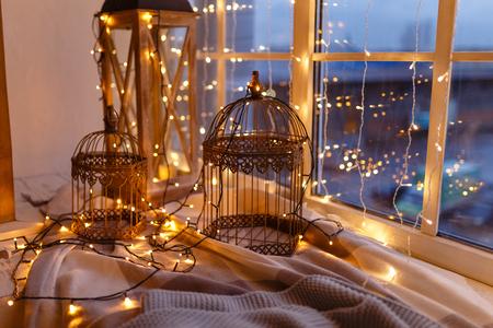 Gabbie per uccelli ricoperte di ghirlanda con luci gialle. Accogliente mattinata invernale o autunnale a casa. Coperta calda, ghirlanda con luci Svedese concept hygge.
