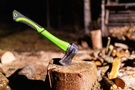 Axe with a strong plastic handle is stuck in a wooden stump against a background of chopped wood. Carpenter's axe for chopping wood is stuck. Sharp axe was stuck in a round old wooden stump Standard-Bild