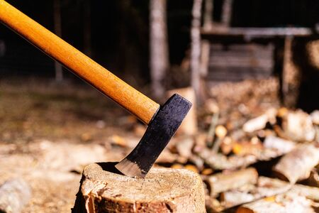 Ax with wooden handle is stuck in wooden stump on background of chopped wood. Carpenter's ax for cutting firewood sticks out in the old tree stump. Sharp ax was stuck in a round old wooden stump Standard-Bild