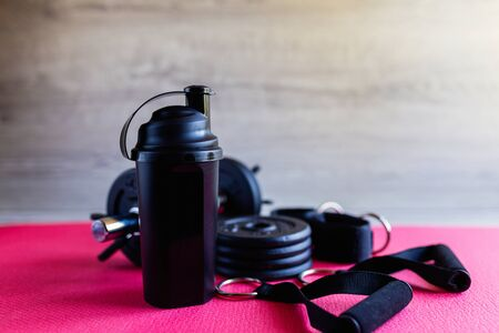 Black protein shaker for mixing on background of sports equipment, black dumbbells, leg ties, handles for traction. Sport fitness bodybuilding healthy lifestyle and weightlifting concept