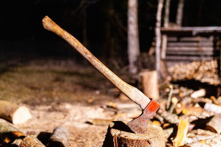 Ax with wooden handle is stuck in wooden stump on background of chopped wood. Old carpenter's ax for cutting firewood sticks out in the old tree stump. Sharp ax was stuck in a round old wooden stump Standard-Bild
