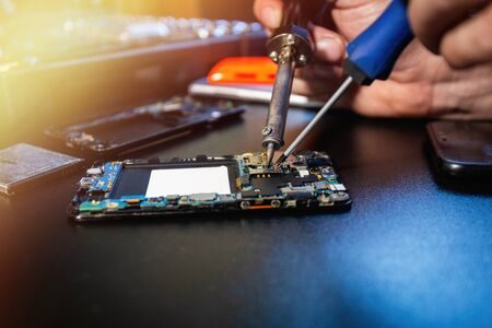 Technician repairs smartphone's motherboard by soldering and using a screwdriver in the lab with flare light. Concept of computer hardware, mobile phone, electronic, repairing, upgrade and technology