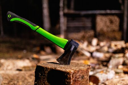 Axe with a strong plastic handle is stuck in a wooden stump against a background of chopped wood. Carpenter's axe for chopping wood is stuck. Sharp axe was stuck in a round old wooden stump 写真素材