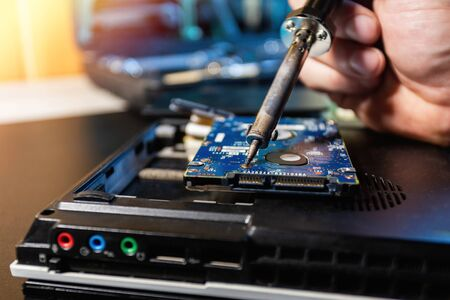 Man repairing hard drive in service center. Repairing and fixing service in lab. Electronics repair service concept. Concept of computer hardware electronic, repairing, upgrade and technology. Standard-Bild