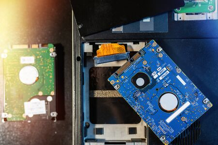 Replacing or installing hdd on an old laptop, on a black background with flare light. Concept of upgrading a laptop computer. The view from the top Standard-Bild - 149322961