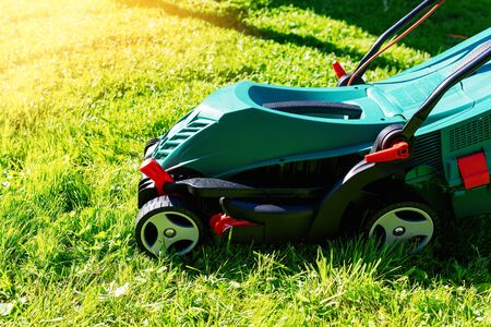 Green electric lawn mower on a freshly mown lawn in the garden against the background of a village house with flare light Standard-Bild - 149790836