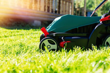 Green electric lawn mower on a freshly mown lawn in the garden against the background of a village house with flare light Standard-Bild - 149789982