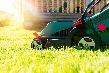 Green electric lawn mower on a freshly mown lawn in the garden against the background of a village house with flare light Standard-Bild - 149790309