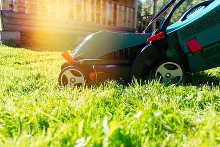 Green electric lawn mower on a freshly mown lawn in the garden against the background of a village house with flare light Standard-Bild - 149789817
