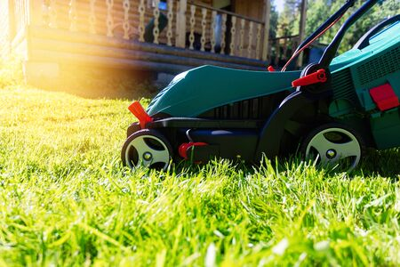 Green electric lawn mower on a freshly mown lawn in the garden against the background of a village house with flare light