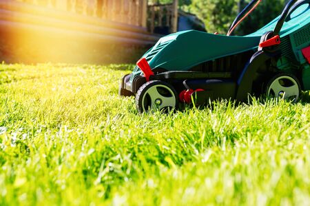 Green electric lawn mower on a freshly mown lawn in the garden against the background of a village house with flare light Standard-Bild - 149789827