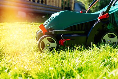 Green electric lawn mower on a freshly mown lawn in the garden against the background of a village house with flare light Standard-Bild - 149790089