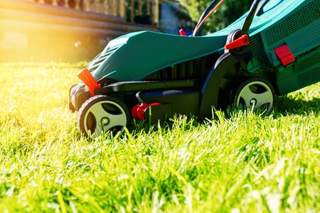 Green electric lawn mower on a freshly mown lawn in the garden against the background of a village house with flare light Standard-Bild - 149790050