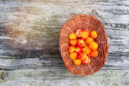 Handful of Cloudberry in wooden basket on an old wooden board background. Healthy diet. Collecting forest ripe cloudberries from the forest. Summer berry. View from the top with flare light Standard-Bild