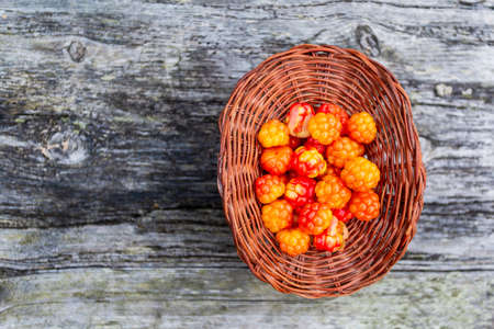 Handful of Cloudberry in wooden basket on an old wooden board background. Healthy diet. Collecting forest ripe cloudberries from the forest. Summer berry. View from the top.