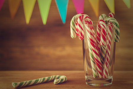 Candy cane in the glass. Christmas sweetness. Closeup. Solid festive caramel. Retro effect.