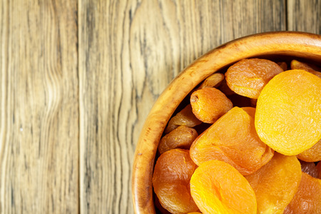 Dried apricots, dried fruits in a wooden plate. Rustic style. Healthy diet. Place for text. Kaisa. Stock Photo
