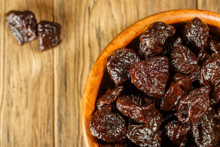 Prunes in a bowl made of beech. Place for text. Dietary food. Stock Photo