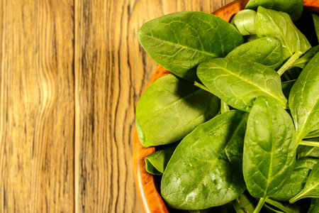 Spinach on the plate, top view. Place for text. Vegetarianism.