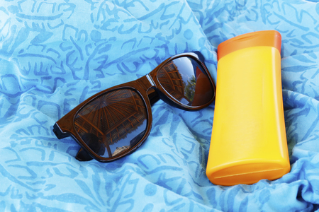 Set safety of the beach. Sunglasses and protective cream. The reflection in the glasses. Oceanic Paradise.