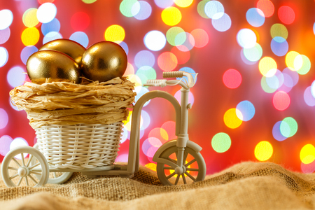 Easter card. Golden eggs in a Bicycle cart. Egg. happy Easter. Stock Photo