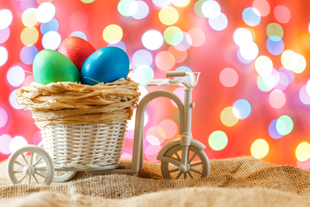 Easter card, colored eggs in the nest. Toy Bicycle with a cart. happy Easter. Pink bokeh background. Stock Photo