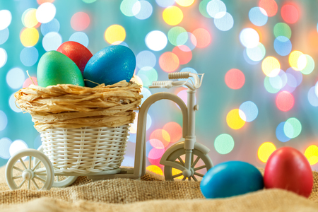 Easter card, colored eggs in the nest. Toy Bicycle with a cart. happy Easter. Delicate blue background. Place for text.