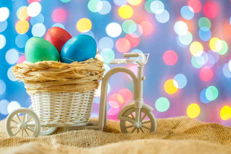 Easter card, colored eggs in the nest. Toy Bicycle with a cart. happy Easter. Blue bokeh background. Toy Bicycle with a cart Stock Photo