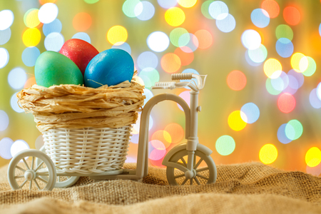 Easter card, colored eggs in the nest. Toy Bicycle with a cart. happy Easter. Yellow delicate bokeh background.