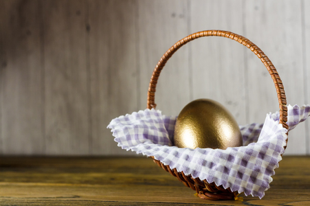 Easter egg in the basket. Wooden background, place for your text. Happy Easter.