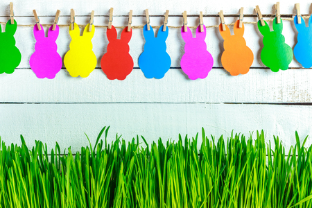 Green grass on wooden background. A lovely garland of bunnies. Place for Your text. Easter card. happy Easter.