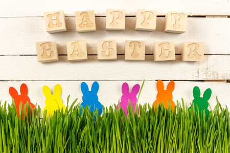 Happy Easter. Cubes with text on a white background. Fresh sprouts and Easter bunnies.  Ready postcard design for Easter. Poster. Stock Photo