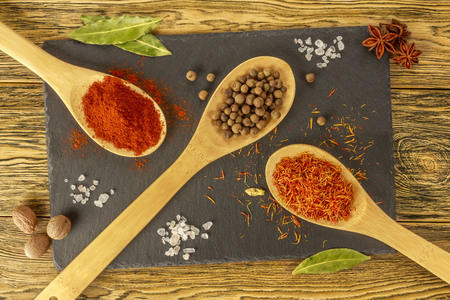 Composition of spices. Seasonings on the kitchen table. Slate Board and wooden spoons. The view from the top. Bright image. Stock Photo